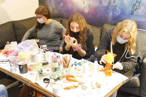 Trzy dziewczyny siedzą przy stole i tworzą ozdoby wielkanocne.