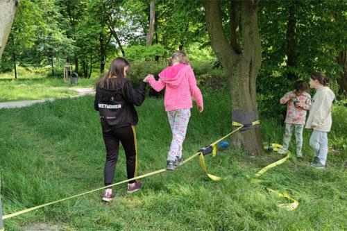 """Dzieci w parku. Nastolatka z """"Mojego Miejsca"""" pomaga młodszemu dziecku w spacerze na slackline."""