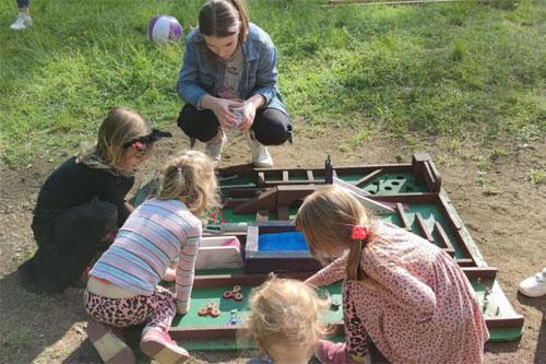 Dzieci w parku. Zabawa przy torze kapslowym.
