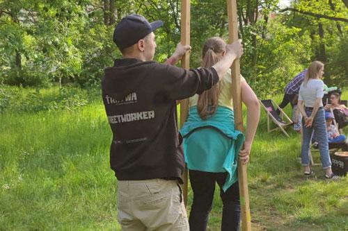 Dzieci w parku. Streetworker z Tratwy pomaga dziewczynce w chodzeniu na szczudłach.