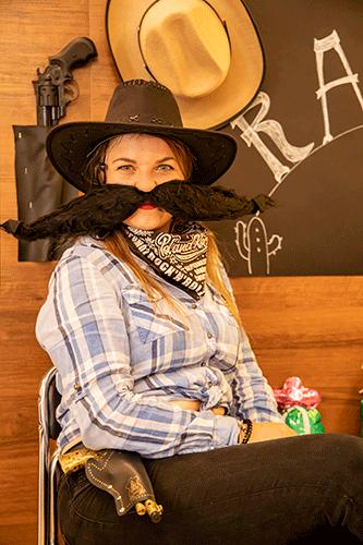 Kobieta przebrana za kowboja siedzi na krześle. Ma dolepione karykaturalne, czarne, sumiaste wąsy.